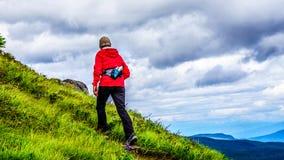 Hogere Vrouw in een rood jasje die omhoog een steile helling wandelen royalty-vrije stock afbeelding