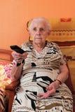 Hogere vrouw en afstandsbediening Stock Foto's
