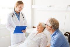 Hogere vrouw en arts met klembord bij het ziekenhuis stock foto's