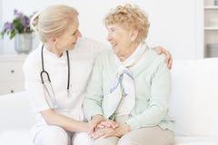 Hogere vrouw en gelukkige arts stock afbeeldingen