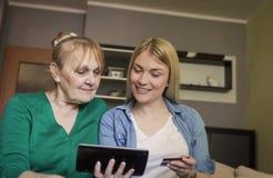 Hogere vrouw en haar volwassen dochter die online thuis winkelen royalty-vrije stock fotografie