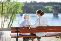 Hogere vrouw en haar volwassen kleindochter in de zomerpark stock foto's