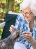 Hogere vrouw en kat Stock Foto's