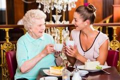 Hogere vrouw en kleindochter bij koffie in koffie Royalty-vrije Stock Afbeelding