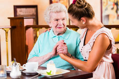 Hogere vrouw en kleindochter bij koffie in koffie Stock Foto