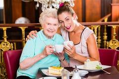 Hogere vrouw en kleindochter bij koffie in koffie Stock Foto's
