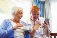 Hogere vrouw en verpleegster die digitale tablet gebruiken Royalty-vrije Stock Foto's