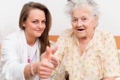 Hogere vrouw en vrouwelijke verpleegster royalty-vrije stock afbeeldingen