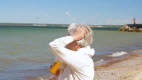 Hogere vrouw het drinken schok op de zomerstrand stock video