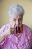 Hogere vrouw het drinken thee Stock Foto