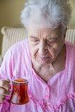 Hogere vrouw het drinken thee Stock Afbeeldingen