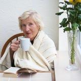 Hogere vrouw het drinken thee binnen stock foto
