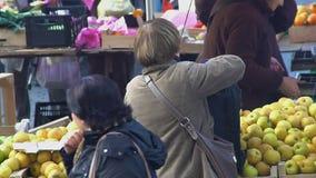 Hogere vrouw het kopen appelen, vele mensen die bij lokale markt, ecovoedsel winkelen stock video