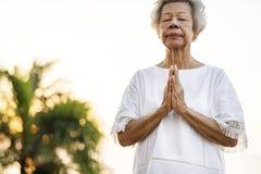 Hogere vrouw het praktizeren yoga in de ochtend stock afbeelding