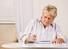 Hogere vrouw het schrijven controles Stock Afbeelding
