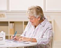 Hogere vrouw het schrijven controles Royalty-vrije Stock Fotografie