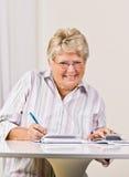 Hogere vrouw het schrijven controles Stock Foto