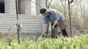 Hogere vrouw het water geven installaties en bloemen van het water geven van pot terwijl het tuinieren het werk stock videobeelden