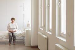 Hogere vrouw in het ziekenhuisruimte Stock Foto