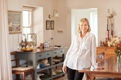 Hogere vrouw kijken die die in haar heldere rustieke keuken wordt ontspannen stock foto's