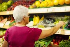 Hogere vrouw in kruidenierswinkelsopslag Royalty-vrije Stock Foto