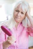 Hogere Vrouw met Borstel Betrokken over Haarverlies stock afbeelding
