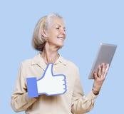 Hogere vrouw met de holdingsvervalsing van tabletpc zoals knoop tegen blauwe achtergrond Royalty-vrije Stock Afbeelding