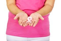 Hogere vrouw met de voorlichtingslint van borstkanker Stock Foto