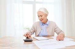 Hogere vrouw met documenten en calculator thuis Stock Foto's