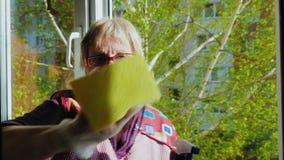 Hogere vrouw met een glimlach die thuiswerk doen - wassen het venster Gebruikt een nevel voor was Buiten het venster, de lente stock video