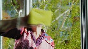 Hogere vrouw met een glimlach die thuiswerk doen - wassen het venster Gebruikt een nevel voor was Buiten het venster, de lente stock videobeelden