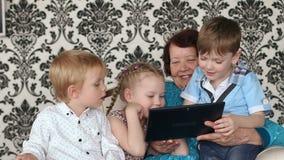 Hogere vrouw met grandkids die met touchpad spelen stock video
