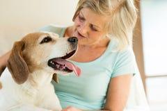 Hogere vrouw met haar hond die thuis ontspannen Royalty-vrije Stock Foto's