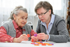 Hogere vrouw met haar oudere zorgverpleegster