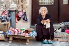 Hogere vrouw met het zitten op de drempel van huis en van de breinaaldenwol sokken voor familie Stock Foto's