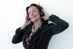 Hogere vrouw met hoofdtelefoons Stock Afbeelding