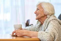 Hogere Vrouw met Kop van Geurige Koffie stock afbeeldingen