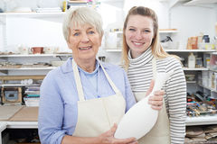 Hogere Vrouw met Leraar Looking At Vase in Aardewerkklasse royalty-vrije stock foto