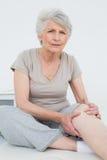 Hogere vrouw met pijnlijke kniezitting op onderzoekslijst royalty-vrije stock afbeeldingen