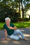 Hogere vrouw met slag in park stock fotografie