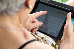 Hogere vrouw met tablet Stock Afbeelding