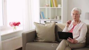 Hogere vrouw met tabletpc en hoofdtelefoons thuis stock footage