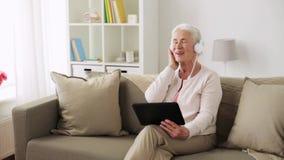 Hogere vrouw met tabletpc en hoofdtelefoons thuis stock videobeelden