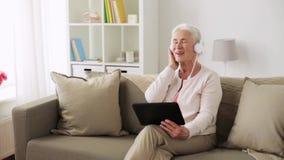 Hogere vrouw met tabletpc en hoofdtelefoons thuis