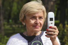 Hogere vrouw met telefoon stock fotografie