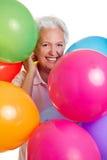 Hogere vrouw met vele ballons Stock Fotografie