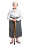 Hogere vrouw met wandelstok die zich op wit bevinden stock foto