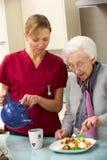 Hogere vrouw met werker uit de hulpverlening die maaltijd thuis eet Royalty-vrije Stock Foto