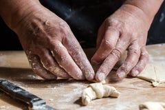 Hogere vrouw, oma, rollende verse eigengemaakte croissants royalty-vrije stock foto's
