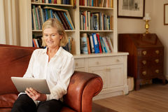 Hogere vrouw op een leerbank met digitale tablet royalty-vrije stock foto